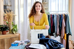 female designer of clothes standing by sewing machine in atelier, attractive tailor after work stand posing, looking at camera smiling. female use measuring tape for sewing and making garments