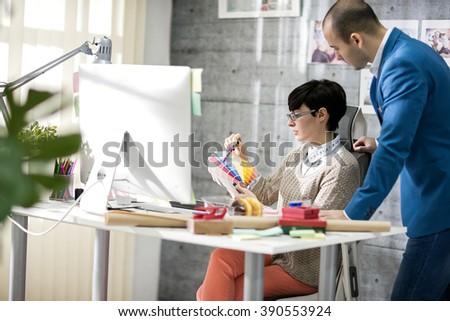 Female designer with male colleagues at design studio #390553924