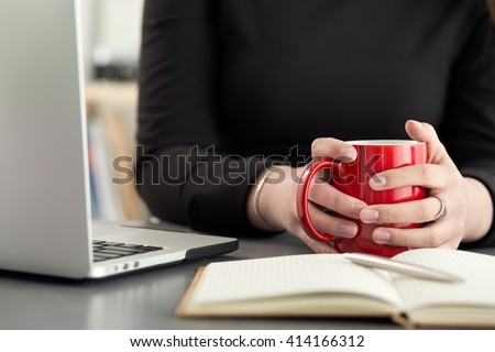 Female designers in office drinking morning tea or coffee. Coffeebreak during hard working day. Girl holding cup of hot beverage.