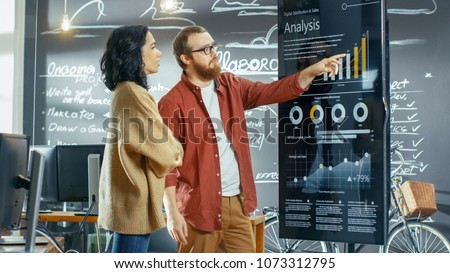 Female Developer and Male Statistician Use Interactive Whiteboard Presentation Touchscreen to Look at Charts, Graphs and Growth Statistics. They Work in the Stylish Creative Office. #1073312795