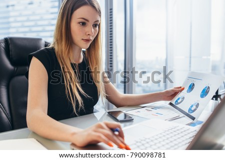 Female director working in office sitting at desk analyzing business statistics holding diagrams and charts using laptop