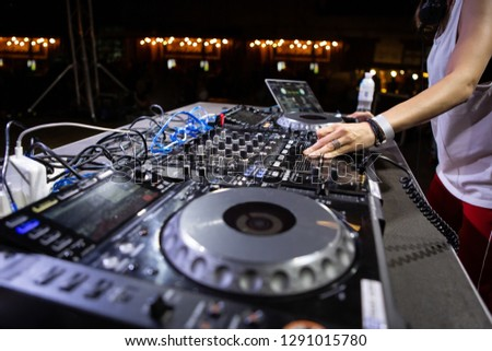 Female disc jockey plays set on stage at summer outdoor music festival. Party dj girl remix popular tracks with professional audio equipment on scene
