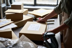 Female distribution warehouse worker or seller packing ecommerce shipping order box for dispatching, preparing post courier delivery package, dropshipping commerce retail shipment service concept.