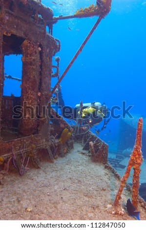 Female diver exploring the superstructure of the gunship, The Tibbetts, off Cayman Brac.