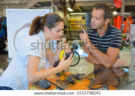 female diver getting advice about diving mouthpieces in diving shop #1515738245