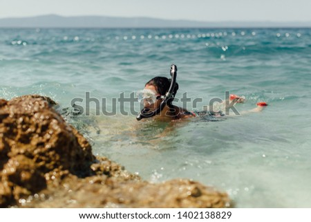 Female diver learning to dive at seashore. Woman wearing diving mask and snorkel snorkeling in sea on hot sunny day. #1402138829