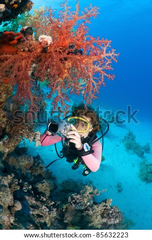 Female diver taking underwater photo.