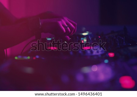 Female dj mixes techno music set on nightclub party in magenta,pink & blue stage lights.Professional dj girl playing musical tracks with turn table and sound mixer in club. Сток-фото ©