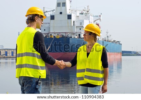 Female docker shaking hands with a male coworker in an industrial harbor, in front of a huge freight ship