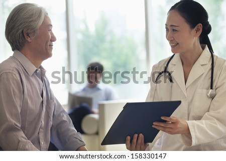 Female Doctor And Patient Discussing Medical Record In The Hospital