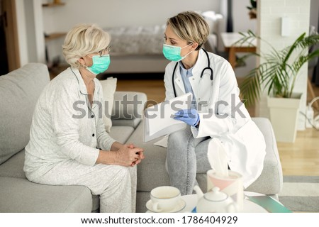 Female doctor and senior woman with protective face masks talking about medical data during a home visit.  Photo stock ©