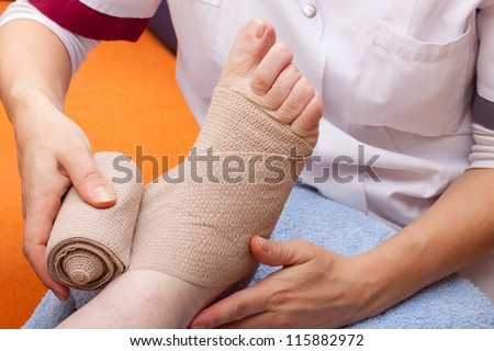 female Doctor bandaged foot of a patient