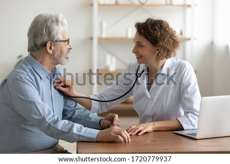 Female doctor cardiologist examining senior male cardiac patient listening checking heartbeat using stethoscope at checkup hospital visit. Old people medicare, elderly healthcare cardiology concept. Foto stock ©