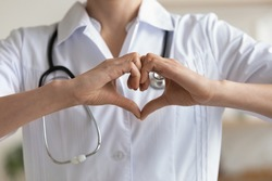 Female doctor cardiologist wearing white coat and stethoscope showing hands heart shape. Cardiology and cardiac healthcare symbol, love and medicine, charity sign, donation concept. Close up view