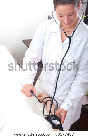Female doctor checking blood pressure with stethoscope and sphygmomanometer