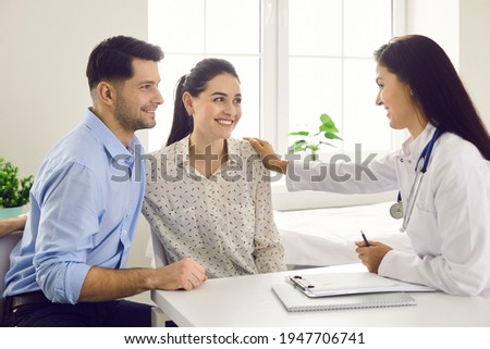 Female doctor consulting young couple patients in fertility clinic about IVF or IUI. Doctor encourages and assures the young couple that everything will be fine. Concept of artificial insemination. Stock photo ©