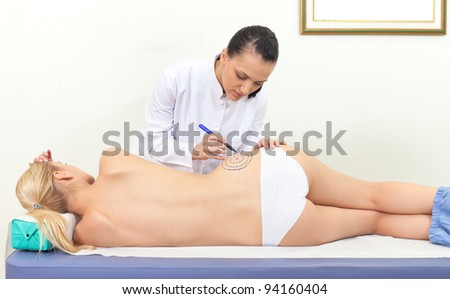 Female doctor drawing correction lines on lying patient waist