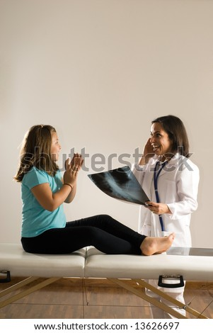 Female Doctor examines a young girl's x-ray while the barefoot girl sits on the examining table. Both people are smiling and appear happy with the results. Vertically framed photograph
