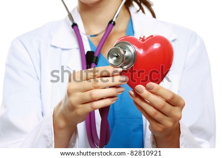 Female doctor examining a red heart with a stethoscope against white background