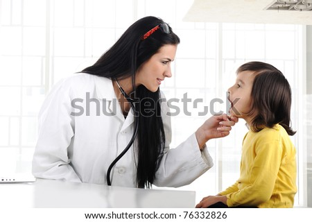Female doctor examining child with tongue depressor