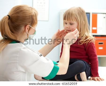 female doctor examining little girl in exam room