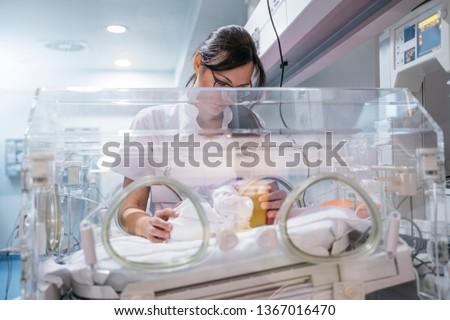 Female doctor examining newborn baby in incubator. Night shift