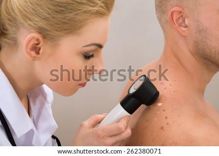 Female Doctor Examining Pigmented Skin With Dermatoscope