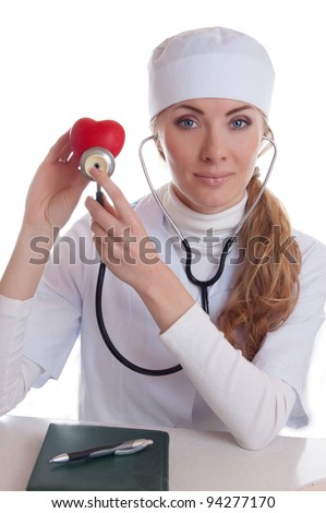 Female doctor examining red heart with stethoscope isolated on white