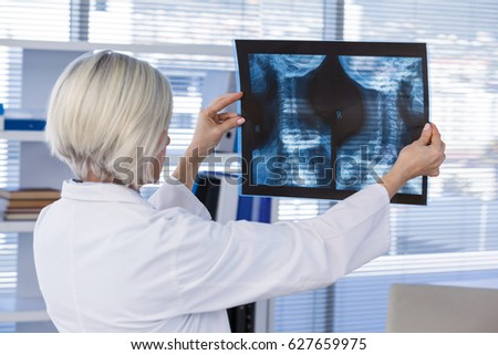 Female doctor examining x-ray report in clinic #627659975