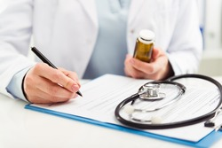 Female doctor filling medical form on clipboard holding ballpoint and medicine bottle. Healthcare and insurance concept.