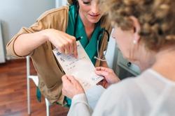 Female doctor giving a prescription to female senior patient