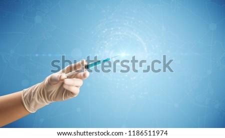 Female doctor hand holding syringe with blue background and shine