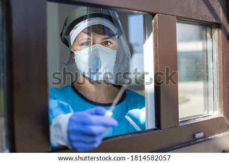 Female doctor holding a nasal swab at a covid-19 testing site window from outside Photo stock ©
