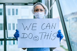 Female doctor holding placard with we can do this text as sing of a support during coronavirus epidemic.