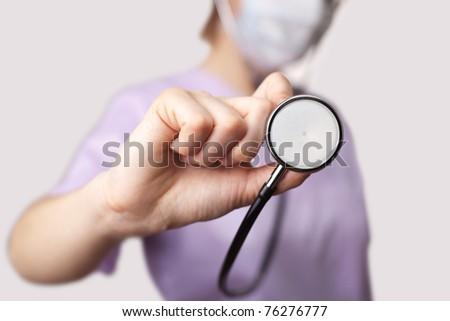 Female doctor holding stethoscope pointed toward camera