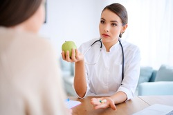 Female doctor holds apple and pills while discussing with patient in the office in hospital. High quality photo