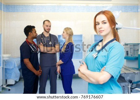 153c86f0eee Female doctor in front of team, looking at camera with medical team in  background.