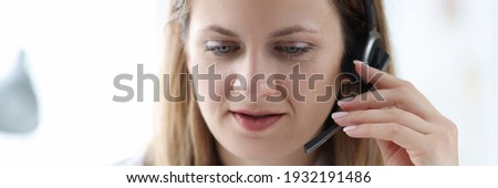 Female doctor in headphones speaking into microphone. Call center work concept