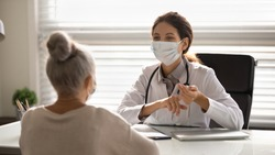 Female doctor in medical facial mask have consultation with elderly patient during covid-19 pandemics. Woman GP in facemask talk consult mature client in clinic or hospital. Coronavirus concept.