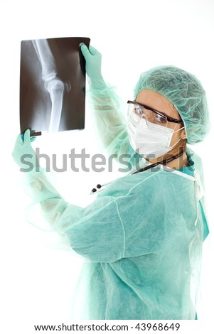 Female doctor in medical mask and protective glasses looking at x-ray, leg