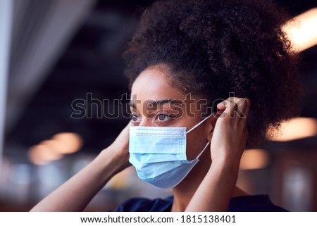 Female Doctor In Scrubs Putting On Face Mask Under Pressure In Busy Hospital During Health Pandemic Foto stock ©