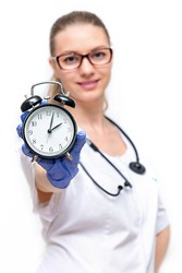 Female doctor in white coat he holds watch in his hand. Time to take care of your health. Isolated on white background. Timely access to doctor, passing medical examinations, prevention of diseases