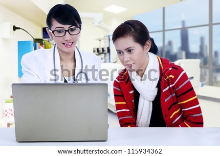 Female doctor is explaining something on her laptop to a patient