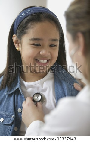 Female doctor listening to young girl's heartbeat