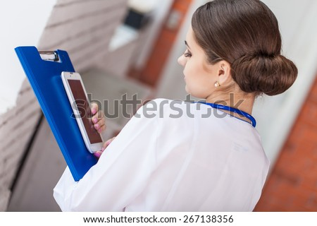 Female doctor looking at medical records on tablet computer at hospital