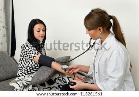 Female doctor measures patient's blood pressure