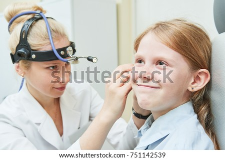 female doctor of ENT ear nose throat at work examining girl ear
