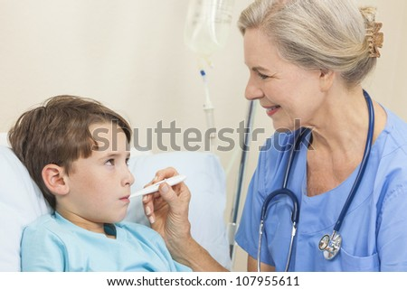 Female doctor or nurse using digital thermometer to take the temperature of young boy child in a hospital bed