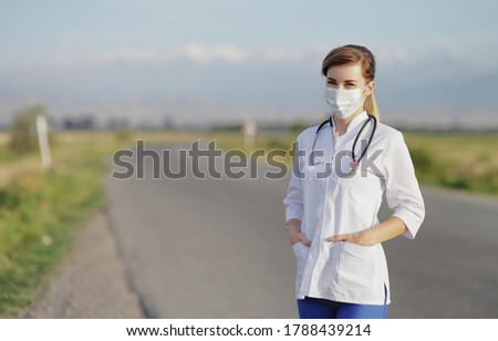 Female doctor or nurse wearing a protective face mask next to a rural road. Foto stock ©