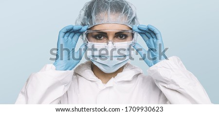 Female Doctor or Nurse Wearing latex protective gloves and medical Protective Mask and glasses on face. Protection for Coronavirus COVID-19
